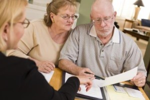 Senior Adult Couple Going Over Papers in Home with Agent